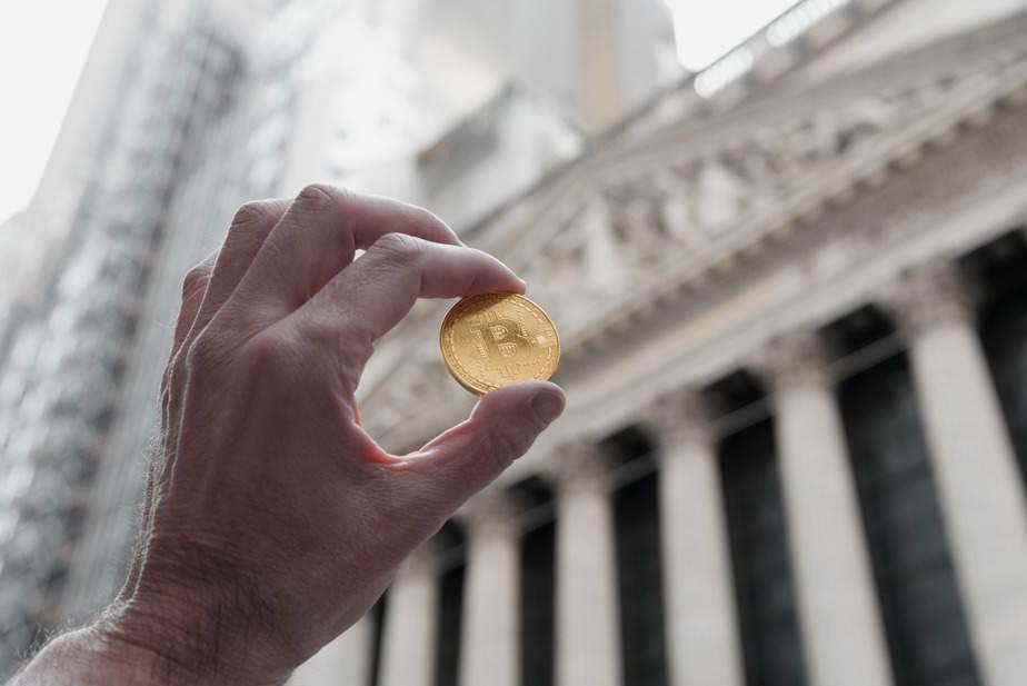 יד אוחזת בביטקוין מול הבורסה לניירות ערך בניו יורק. צילום: שאטרסטוק